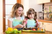 Cute woman with child daughter preparing fish in kitchen — Stock Photo