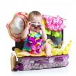 Baby girl sitting in suitcase with things for vacation travel — Stock Photo #72809037