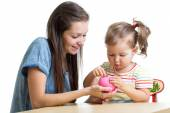Mother and daughter put coins into piggy bank — Stock Photo
