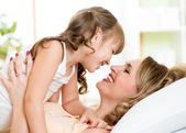 Happy mom playing with her kid in bed enjoying  sunny morning in home bedroom — Stock Photo