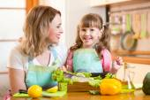 Happy mom and kid cooking healthy food in kitchen — Stock Photo
