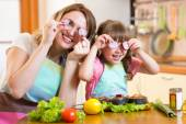 Mother and daughter playing with vegetables in kitchen, healthy food — Stock Photo