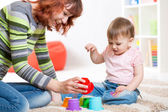 Cute mother and her daughter playing together indoor — Stock Photo