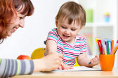 Child and mother draw with colorful pencils — Stock Photo