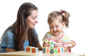 Child girl and mom have fun playing cubes toys — Stock Photo