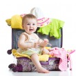 Baby girl sitting in suitcase with things for vacation travel — Stock Photo #73633515