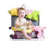 Baby girl sitting in suitcase with things for vacation travel — Stock Photo