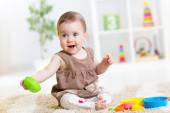 Baby girl playing with colorful toys — Stock Photo