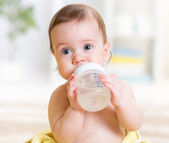 Cute baby holding bottle and drinking water — Stock Photo