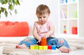 Kid girl playing wooden block toys — Stock Photo
