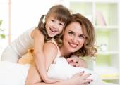 Woman and kid girl in bed playing and smiling — Stock Photo