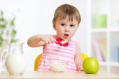 Little girl eating cornflakes with milk in home — Stock Photo