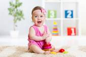 Cute baby playing with colorful toy pyramid — Stock Photo