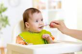 Mother feeding baby with spoon — Stock Photo