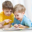 Kids brothers practice reading together looking at book laying on the floor — Stock Photo #76789491