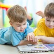 Lovely children brothers reading a book, on the floor at home — Stock Photo #77041789