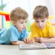 Lovely children brothers reading a book, on the floor at home — Stock Photo #77041877