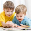 Cute little boys read book together — Stock Photo #77041901