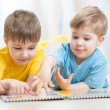 Lovely children brothers reading a book, on the floor at home — Stock Photo #77041921