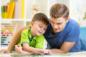 Father and son read together sitting on the floor. Kid reading story book with his dad at home. — Stock Photo