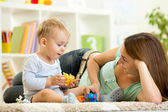 Child and his mom play zoo holding animal toys — Stock Photo