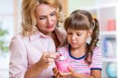 Mother and her daughter putting coins into piggy bank — Stock Photo