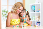Mother and her daughter playing with cubes — Stock Photo