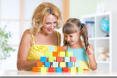 Middle aged woman helping her preschooler daughter build  tower from colorful building blocks as they sit together at table at home — Stock Photo