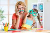 Child with mother have a fun cutting out scissors paper in preschool — Stock Photo