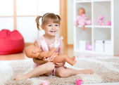 Smiling little girl playing with a doll at home — Stock Photo
