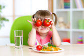 Little girl playing with vegetables — Stock Photo