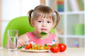 Kid eating healthy food in kindergarten or at home — Stock Photo