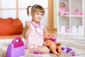 Little girl plays doctor examining a doll patient with toy stethoscope — Stock Photo