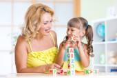 Smiling mother assisting girl in playing block game — Stock Photo