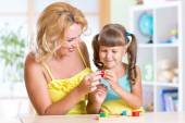 Child with mother playing together at table — Stock Photo
