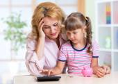 Family - middle aged woman and her daughter with pink piggy bank and calculator — Stock Photo