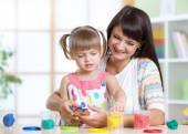 Happy child and mother sitting at table and playing with colorful clay toy — Stock Photo
