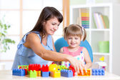 Child girl playing construction set with mother — Stock Photo