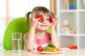 Kid girl having fun with food vegetables in children room — Stock Photo