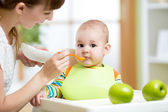 Happy mother spoon feeding her baby child — Stock Photo