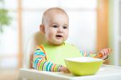 Baby child sitting in chair with a spoon — Stock Photo