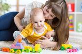 Child boy and mother playing together with toys at home — Stock Photo