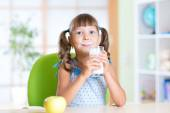 Little girl having breakfast: drinking a glass of milk — Stock Photo