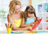 Happy woman teaching preschooler kid do craft items in daycare center — Stock Photo