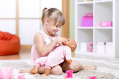 Girl playing with her baby-doll — Stock Photo