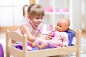 Kid playing a doctor with doll — Stock Photo