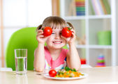 Child with tomatoes. Happy girl with vegetables at home. — Stock Photo