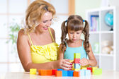 Middle aged woman helping her daughter build  tower from colorful building blocks — Stock Photo