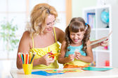 Child with woman cutting out scissors paper in preschool — Stock Photo