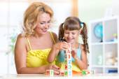 Child and mom playing wooden toys at home — Stock Photo